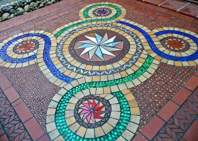 An ancient guilloche pattern, or Quincunx, reinterpreted with scrap tile, Heineken and Skyy Vodka bottles.